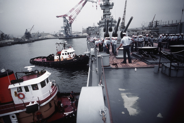 Tug boats maneuver the battleship USS NEW JERSEY (BB 62) away from the pier. The NEW JERSEY, after recently completing renovation and modernization, is departing for sea trials prior to reactivation in January 1983