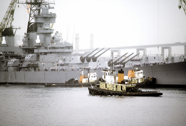 Tugboats maneuver into positions to tow the battleship USS NEW JERSEY (BB-62) from the dock for sea trials