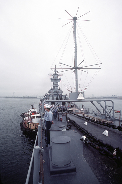 Tugs, on the starboard side, assist the battleship USS NEW JERSEY (BB 62) away from the pier. The NEW JERSEY, after recently completing renovation and modernization, is departing for sea trials prior to reactivation in January 1983