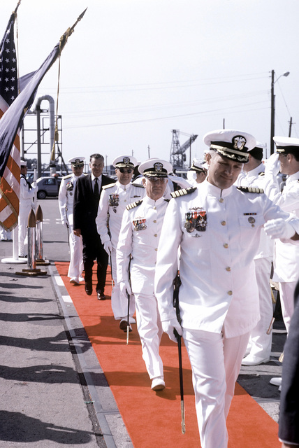 Two Navy captains salute as they come aboard the nuclear-powered attack submarine USS HOUSTON (SSN-713) for the ship's commissioning ceremony. VADM Steven A. White, commander, Submarine Force, U.S. Atlantic Fleet; G. A. Sawyer, assistant secretary of the Navy; and RADM Joseph F. Frick, commander, Naval Base Norfolk are following behind them