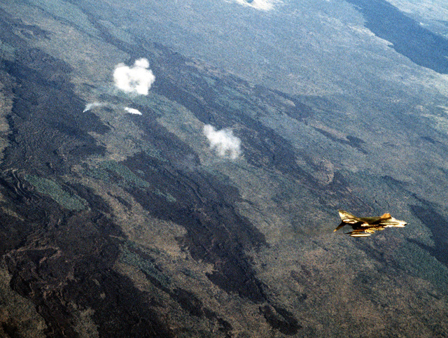 An aerial view of the range as an F-4 Phantom II aircraft flies over a bomb target. The aircraft is assigned to the 3rd Tactical Fighter Wing, involved in Exercise Opportune Journey 4