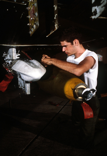 An airman secures the attachment of a Mark 82 500-pound laser-guided bomb to an F-4 Phantom II aircraft. The airman is assigned to the 3rd Munitions Maintenance Squadron, involved in Exercise Opportune Journey 4
