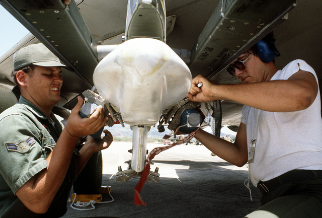 SSGT Darrell J. Bucy, left, and A1C Scott Catino, right, load Bomb Disposal Unit bombs onto an F-4 Phantom II aircraft. The airmen are assigned to the 3rd Munitions Maintenance Squadron, involved in Exercise Opportune Journey 4