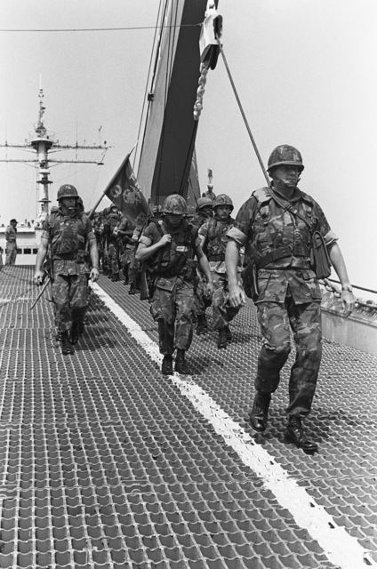 Colonel James M. Mead, 32nd Marine Amphibious Unit commander, leads Marines down the bow ramp of the tank landing ship USS MANITOWOC (LST 1180) to begin their to participation in a multinational peacekeeping operation