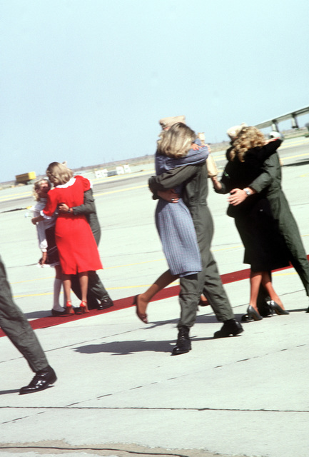 A-7E Corsair aircraft pilots are greeted by their wives upon return home from aboard the aircraft carrier USS RANGER (CV-61). The pilots are from the Light Attack Squadrons 25 (VA-25) and 113 (VA-113)