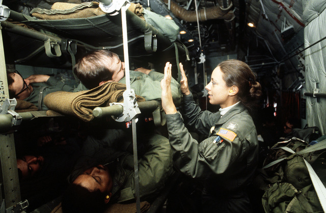 """A flight nurse from the 68th Aeromedical Evacuation Squadron, Norton Air Force Base, Calif., assists a """"patient"""" on board a C-141 Starlifter aircraft during exercise Reforger '81"""