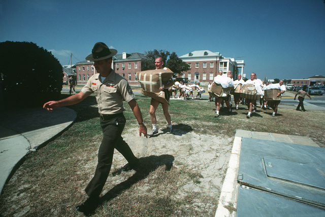 A Marine drill instructor strides across the grass as his class of Aviation Officer Candidates struggles to keep up with him. The candidates are in the first of 14 weeks of training
