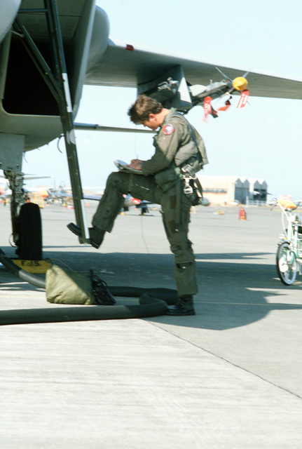 A pilot completes a pre-flight check of his F-15 Eagle aircraft during training exercise Cope North '83-1. The exercise, held at Chitose Air Base, is designed to prepare pilots for air-to-air combat