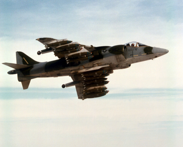 Air-to-air right underside view of a U.S. Marine Corps AV-8B Harrier II aircraft. The aircraft is equipped with general purpose bombs