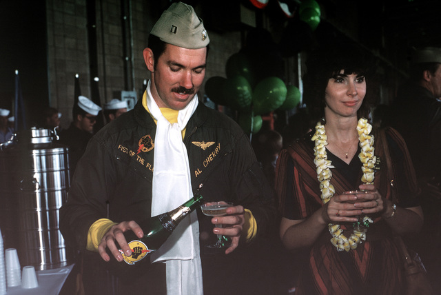 An A-7E Corsair II aircraft pilot, accompanied by his wife, celebrates at the welcome home ceremony. The aircrews, from the Light Attack Squadrons 25 (VA-25) and 113 (VA-113), return from aboard the aircraft carrier USS RANGER (CV-61)