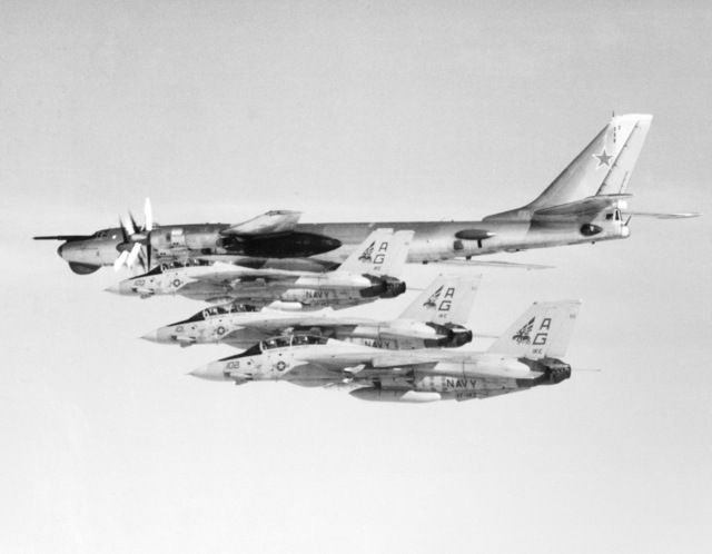 An air-to-air left side view of three Fighter Squadron 143 (VF-143) F-14A Tomcat aircraft as they intercept and escort a Soviet Bear reconnaissance aircraft. The Soviet aircraft was in the area to observe the operations of the nuclear-powered aircraft carrier USS DWIGHT D. EISENHOWER (CVN-69)