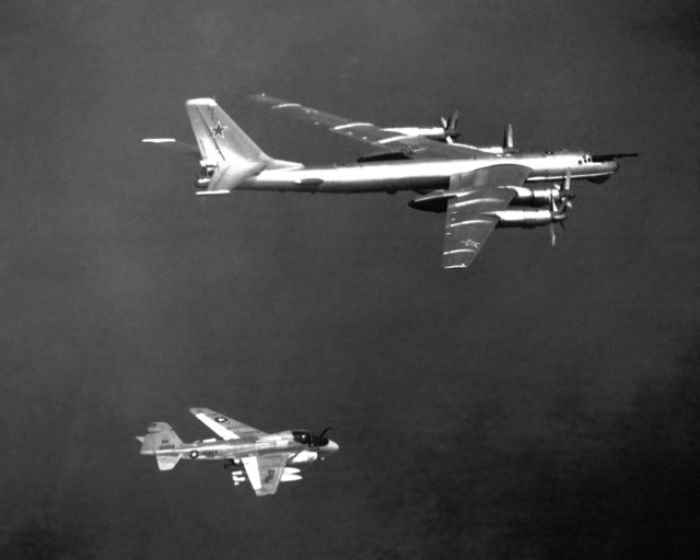 An air-to-air right side view of a Medium Attack Squadron 95 (VA-95) A-6E Intruder aircraft, assigned to the nuclear-powered aircraft carrier USS ENTERPRISE (CVN 65), escorting a Soviet Tu-142 Bear-D aircraft