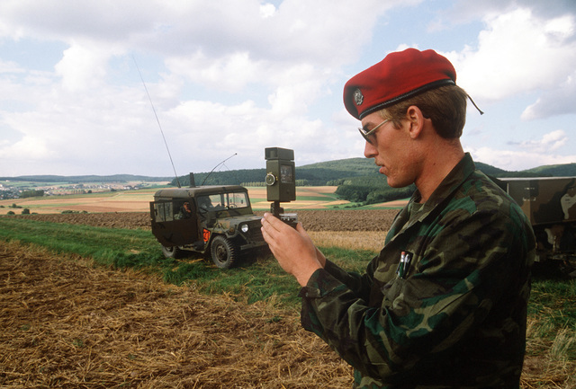 An Army infantryman takes a compass reading in the area where three containers of c-rations are to be dropped by parachute for troops in the field during Exercise Reforger '81