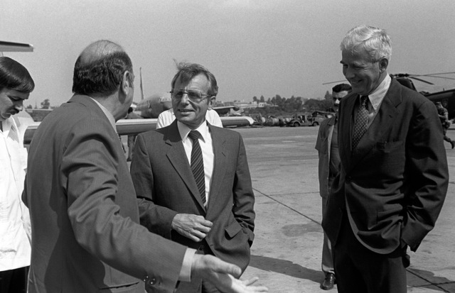 Assistant Secretary of Defense Frank Carlucci, center, is greeted by American Ambassador to Lebanon, Robert Sherwood Dillon, and other dignitaries upon his arrival at Beirut International Airport. Marines from the 32nd Marine Amphibious Unit have been deployed here to participate in a multinational peacekeeping operation