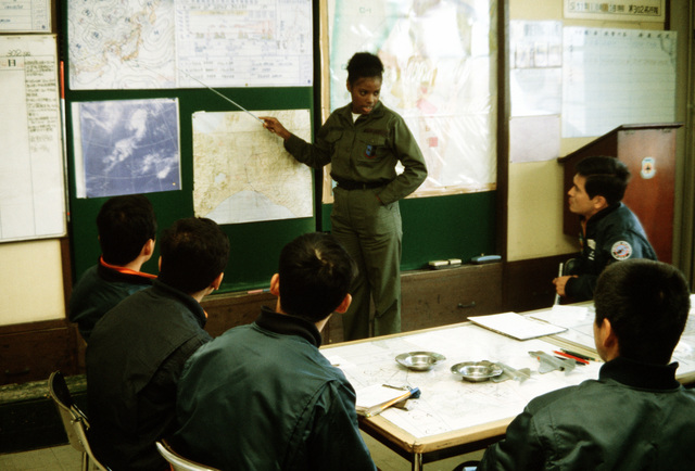 CPT Cheryl B. Aultman gives a weather briefing to members of the 302nd Tactical Fighter Squadron, Japanese Air Self Defense Force, during training exercise Cope North '83-1. The exercise was held at Chitose Air Base