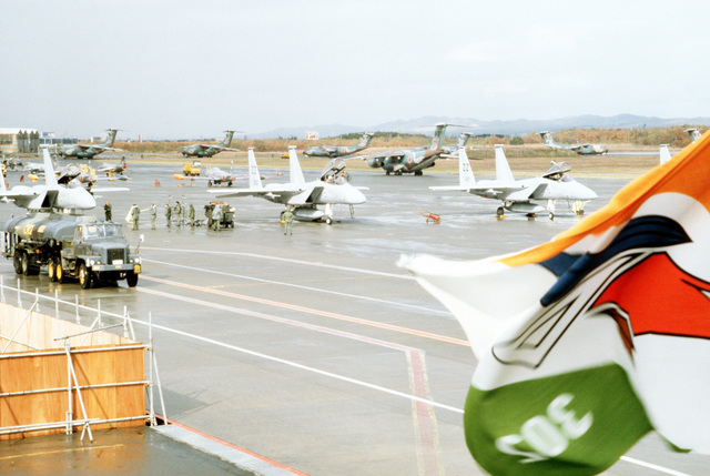 F-15 Eagle aircraft are serviced on the flight line at Chitose Air Base during training exercise Cope North '83-1. Japanese Air Self Defense Force C-130 Hercules aircraft can be seen in the background