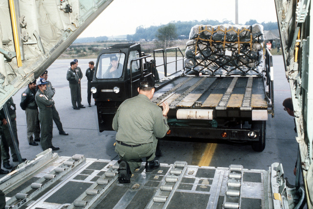 Ground crewmen move a K-loader into position to load pallets onto a C-141 Starlifter aircraft during Exercise Reforger '81