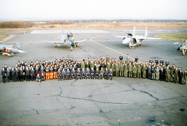 Members of the Japanese Air Self Defense Force and United States Air Force who participated in training exercise Cope North '83-1 pose for a group photo on the flight line. The aircraft parked on the runway behind them (from left to right) are an F-104 Starfighter, an F-4 Phantom II and an F-15 Eagle