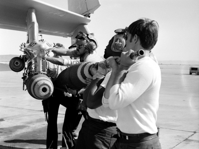 Ordnancemen from Carrier Air Wing 15 (CVW-15) arm bombs being loaded aboard an aircraft
