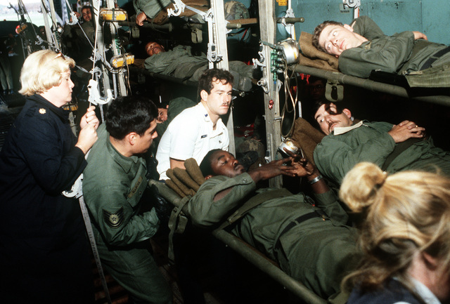 "Reserve medics from the 1ST Aeromedical Evacuation Squadron, McGuire Air Force Base, New Jersey, assist ""patients"" on board a C-141 Starlifter aircraft during Exercise Reforger '81"