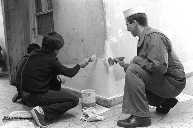 "Sonar Technician 3rd Class Michael Cocca of the guided missile destroyer USS PREBLE (DDG-46) helps residents of ""Ciudad de Ninos"" (a home for boys modeled after Boys Town USA) with painting and repairs during exercise Unitas XXIII '82"