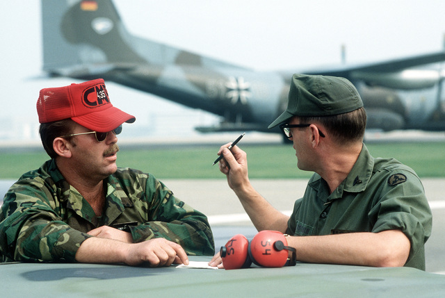 SSGT J. Jackson, 435th Combat Mobility Branch, Rhein-Main Air Base, West Germany, goes over the equipment loading plan with CPT George Kauffman from the 32nd Combat Mobility Hospital during Exercise Reforger '81. A German C-160 aircraft can be seen in the background