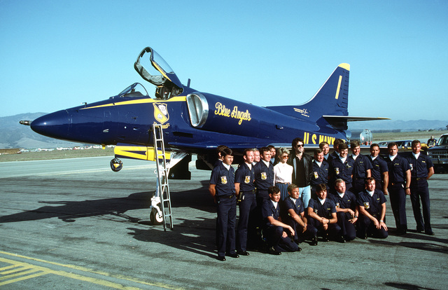 Entertainers John Travolta and Olivia Newton John, center, along with enlisted crew of the Navy's Blue Angels flight demonstration team pose in front of an A-4F Skyhawk aircraft parked on the apron. The Blue Angels performed during a local air show