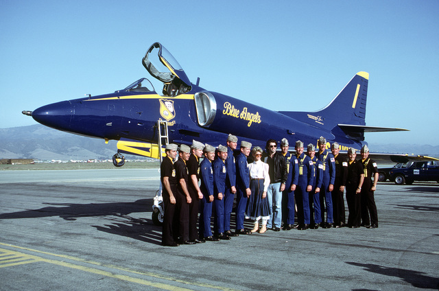 Entertainers John Travolta and Olivia Newton John, center, along with pilots of the Navy's Blue Angels flight demonstration team pose in front of an A-4F Skyhawk aircraft parked on the apron. The Blue Angels performed during a local air show