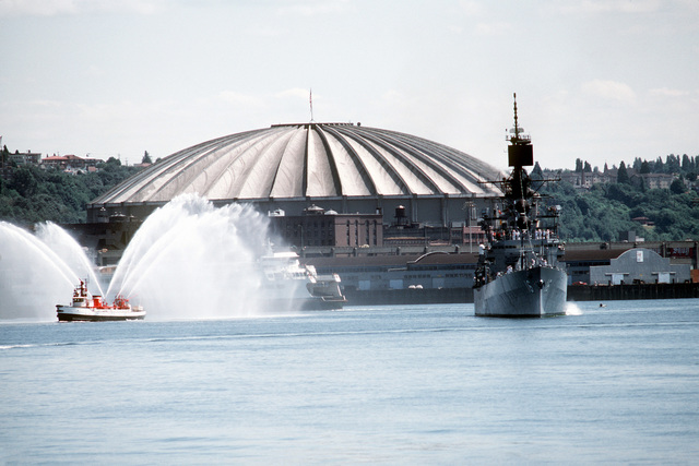 A starboard bow view of the guided missile cruiser USS LEAHY (CG-16), arriving in port during the Seattle Sea Fair 1982. A tug boat sprays water into the air to welcome it. The Kingdome Stadium is visible in the background
