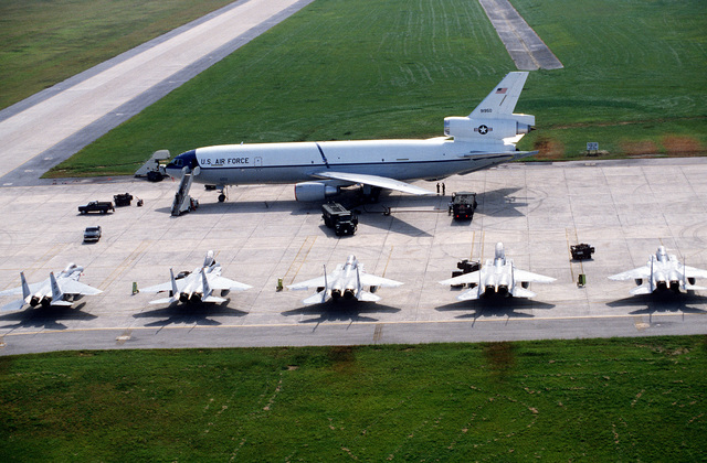 A left side view of a KC-10A Extender aircraft and a rear view of five F-15 Eagle aircraft on the flight line during William Tell Exercise