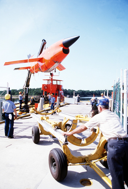 A crane aboard the U.S. Air Force missile recovery ship (MR-85 1603) lifts a Firebee drone from the deck of the ship to a trailer on the dock. The drone was recovered from the water after having served as a target for aircraft participating in the air-to-air combat training exercise William Tell '82