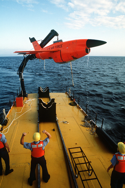 A crane aboard the U.S. Air Force missile recovery ship (MR-85 1603) lifts a Firebee drone from the ocean. The drone landed in the water after completion of a mission as a target for aircraft participaing in the air-to-air combat training exercise William Tell '82