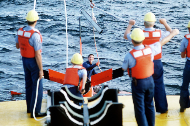 A diver from the U.S. Air Force missile recovery ship (MR-85 1603) attaches a recovery sling to a Firebee drone. The drone parachuted into the ocean after completion of a mission as a target for aircraft participaing in the air-to-air combat training exercise William Tell '82
