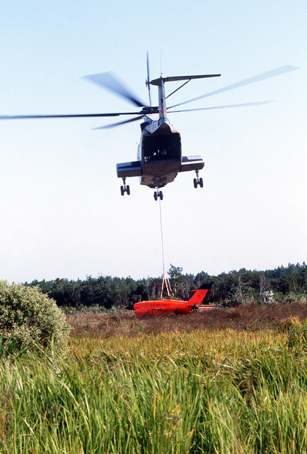 A ground-to-air rear view of a CH-3 Sea King helicopter recovering a Firebee drone during the air-to-air combat training exercise William Tell '82