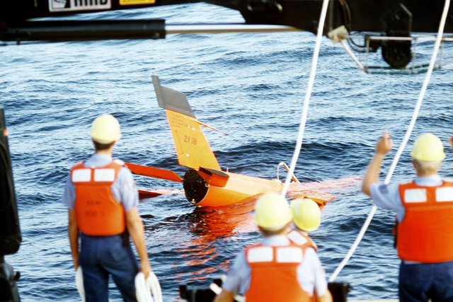 Crewmen aboard the U.S. Air Force missile recovery ship (MR-85 1603) prepare to attach a recovery sling to a Firebee drone. The drone parachuted into the ocean after completion of a mission as a target for aircraft participating in the air-to-air combat training exercise William Tell '82