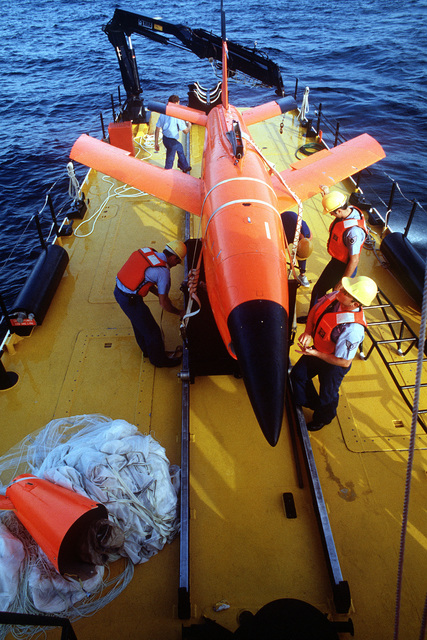 Crewmen aboard the U.S. Air Force missile recovery ship (MR-85 1603) secure a Firebee drone to a cradle on the deck. The drone parachuted into the ocean after completion of a mission as a target for aircraft particpating in the air-to-air combat training exercise William Tell '82