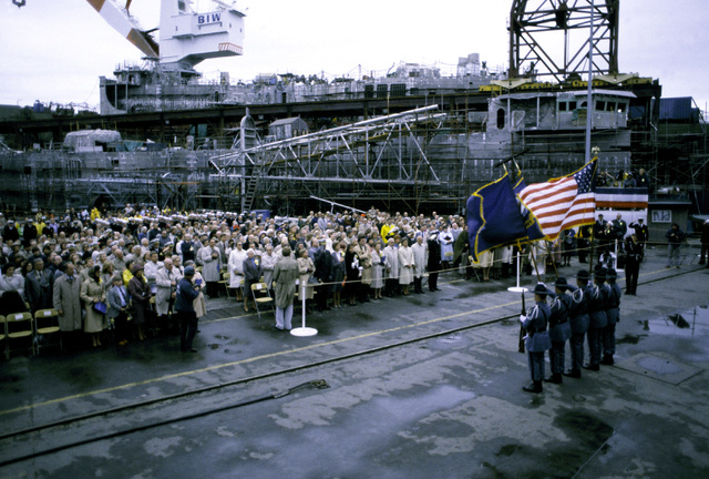 Guests attending the commissioning ceremony for the guided missile frigate USS AUBREY FITCH (FFG-34) stand for the playing of the National Anthem