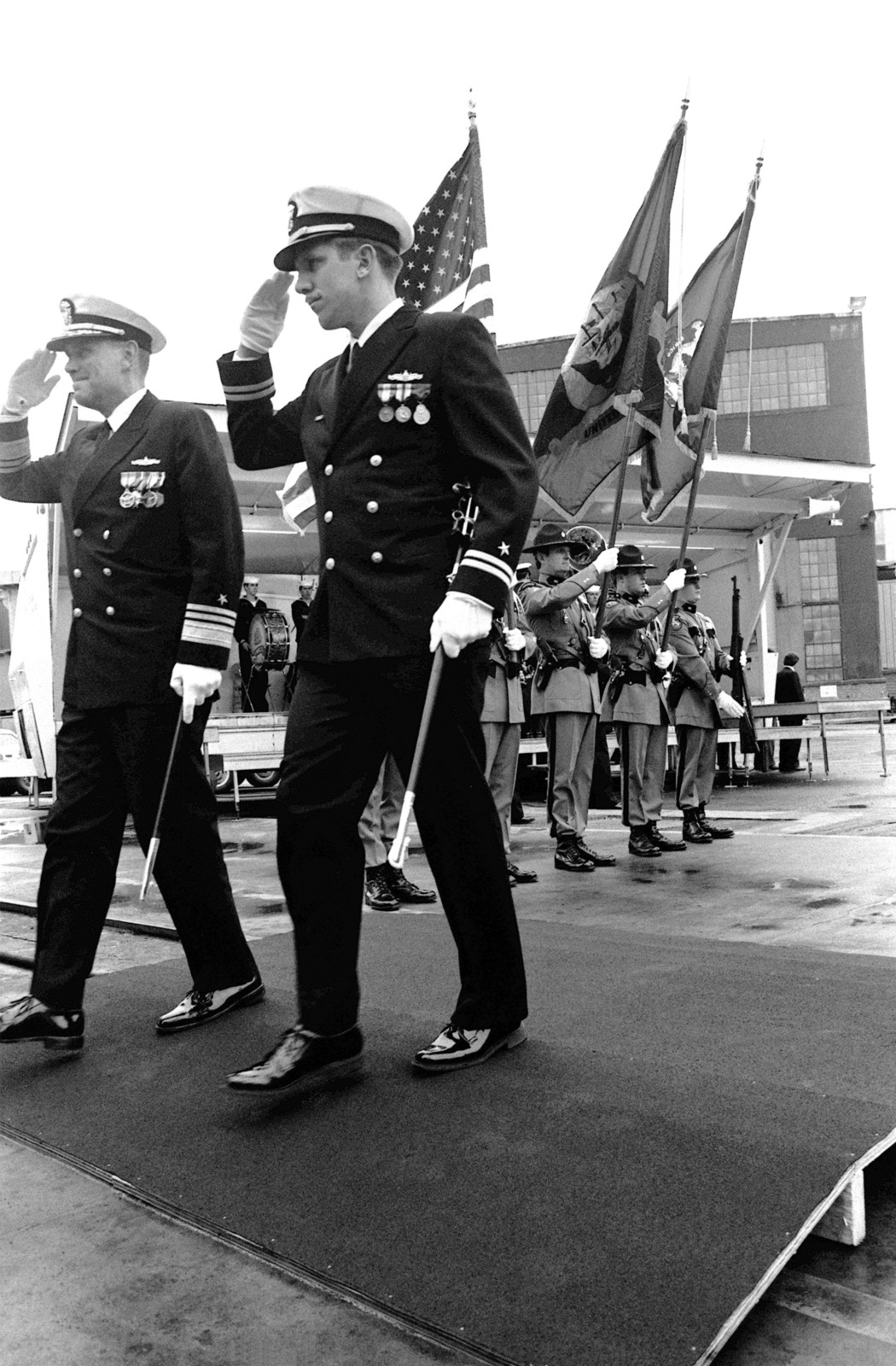 VADM Robert T. Monroe, director, Research, Development, Test and Evaluation, along with a fellow officer, salutes the colors prior to boarding the guided missile frigate USS AUBREY FITCH (FFG-34) for its commissioning ceremony