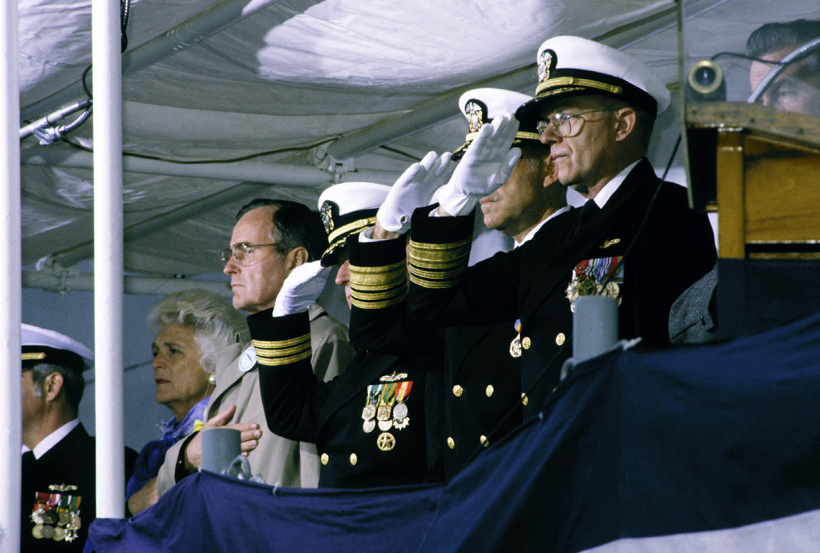 Vice President George Bush and his wife Barbara stand with other distinguished speakers during the playing of the National Anthem, as the commissioning ceremony for the guided missile frigate USS AUBREY FITCH (FFG-34) begins