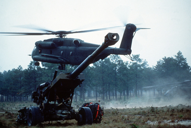 A Marine CH-53E Sea Stallion helicopter delivers supplies to the 10th Marine Regiment in the field. AN M-198 155mm howitzer is in the foreground