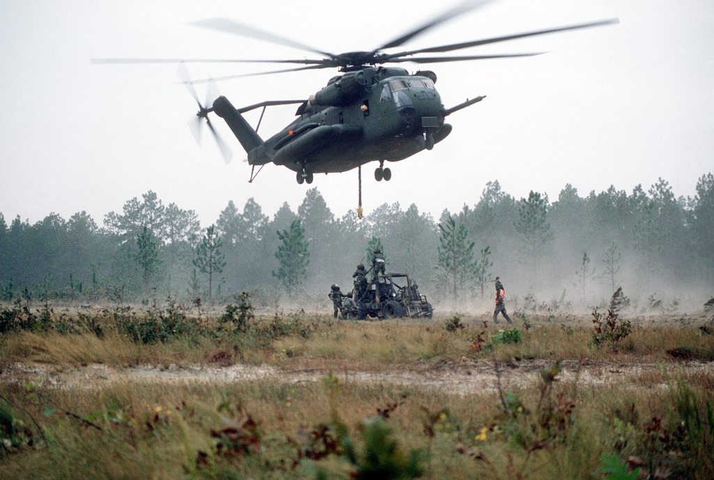 A Marine CH-53E Sea Stallion helicopter prepares to airlift a forklift during the 10th marine Regiment field training exercise with the 155mm M-198 howitzer