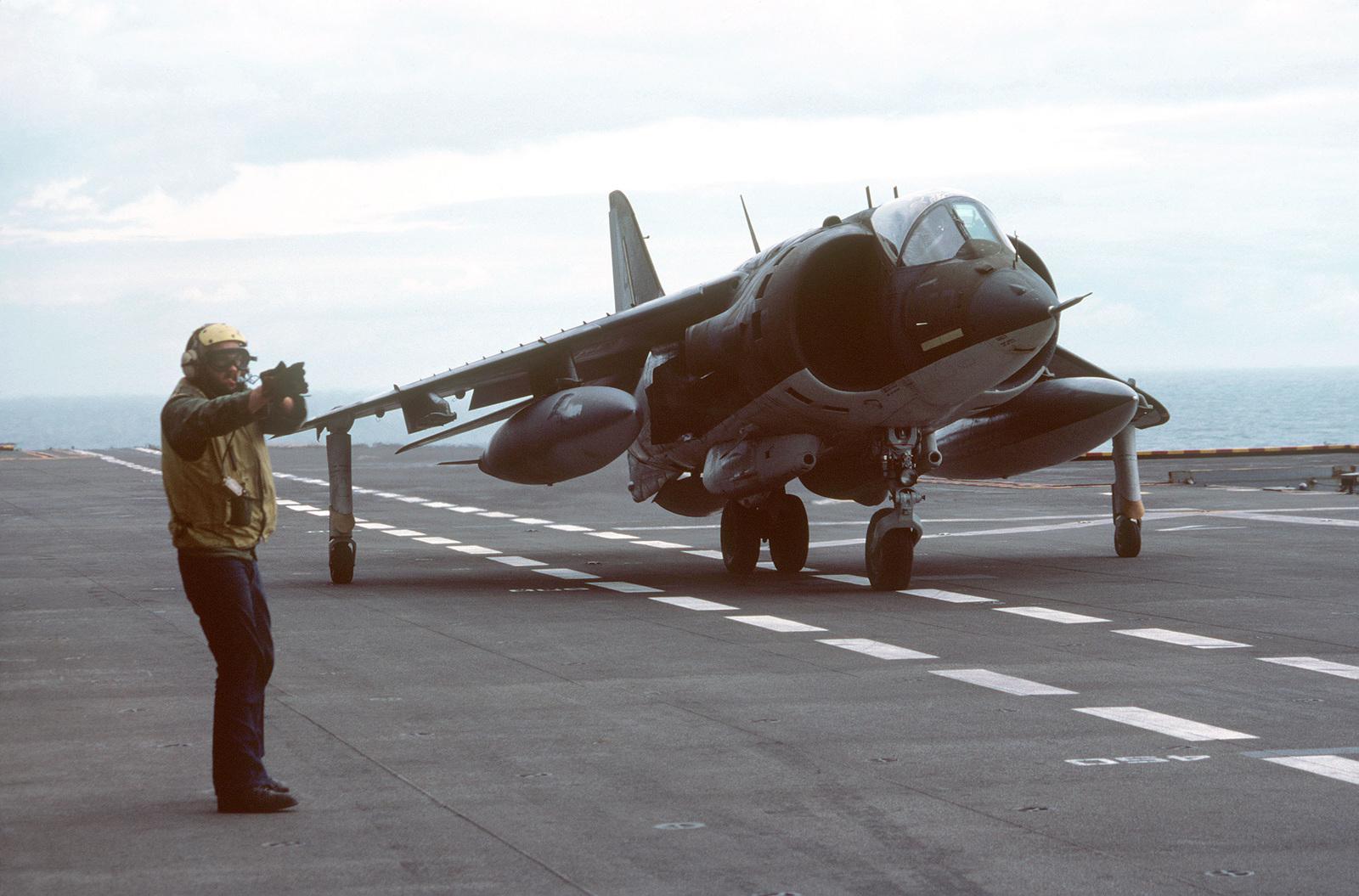 A flight deck crewman signals to the pilot of an AV-8A