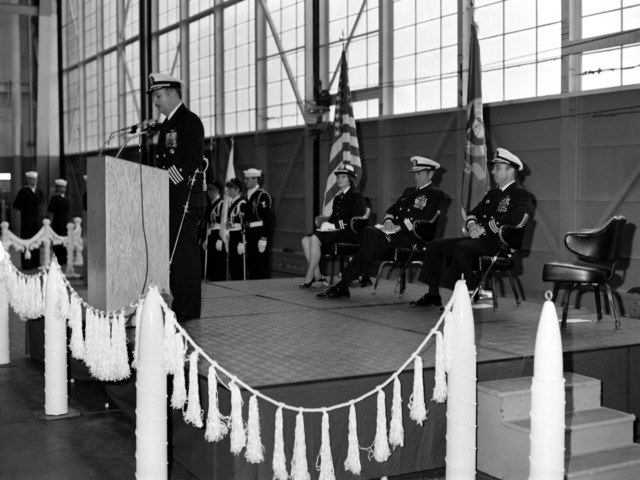 CAPT David D. Williams reads his orders as new commanding officer of Attack Squadron 128 (VA-128), during the change of command ceremony