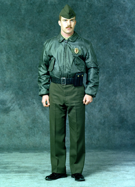 A Marine SGT. is dressed in a military police winter uniform. He is wearing green trousers, a green jacket, a garrison cap, a police badge and a pistol belt