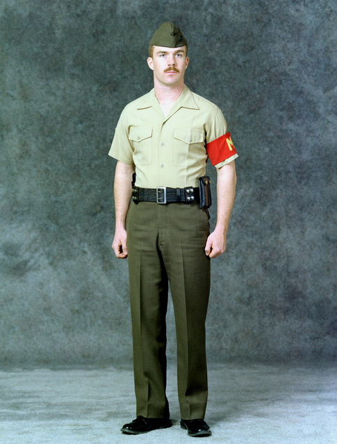 A Marine SGT. is dressed in the military police (MP) summer uniform. He is wearing green trousers, a khaki shirt, an MP arm band and a pistol belt