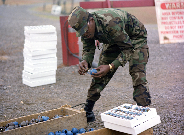 A member of the 1ST Brigade inserts a fuse into an M-69 blue practice grenade during training at the Army Armor Center