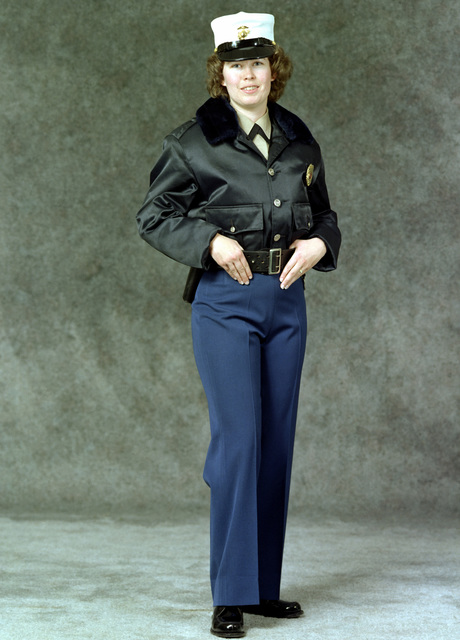 A woman Marine Lance CPL. is dressed in a military police (MP) winter uniform. She is wearing blue slacks, brown jacket, a white cap, a pistol belt and a police badge