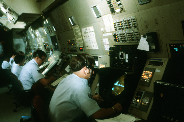 Air traffic controllers monitor radar scopes at the Travis Air Force Base Control Center