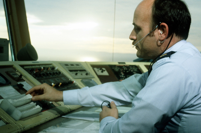 LT. Dan D'Innocenti, an air traffic controller, operates a control panel in the tower of the Oakland Airport