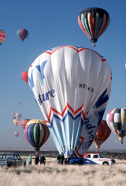 Members of the Navy Balloon Team combine their efforts to release hot air from the balloon upon landing during the 10th anniversary of the Albuquerque International Balloon Fiesta